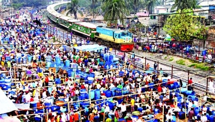 A fish market has been set up across railway track in the capital's Kawran Bazar area violating railway law. This photo taken on Saturday shows that traders sell fish at the market while train is passing through the rail track dangerously.