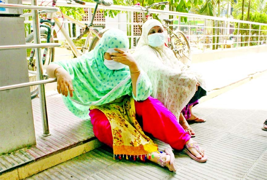 Two women bring a Covid-positive patient to Dhaka Medical College Hospital in the capital but due to lack of bed they had to wait for hours outside the facility. This photo was taken on Tuesday.