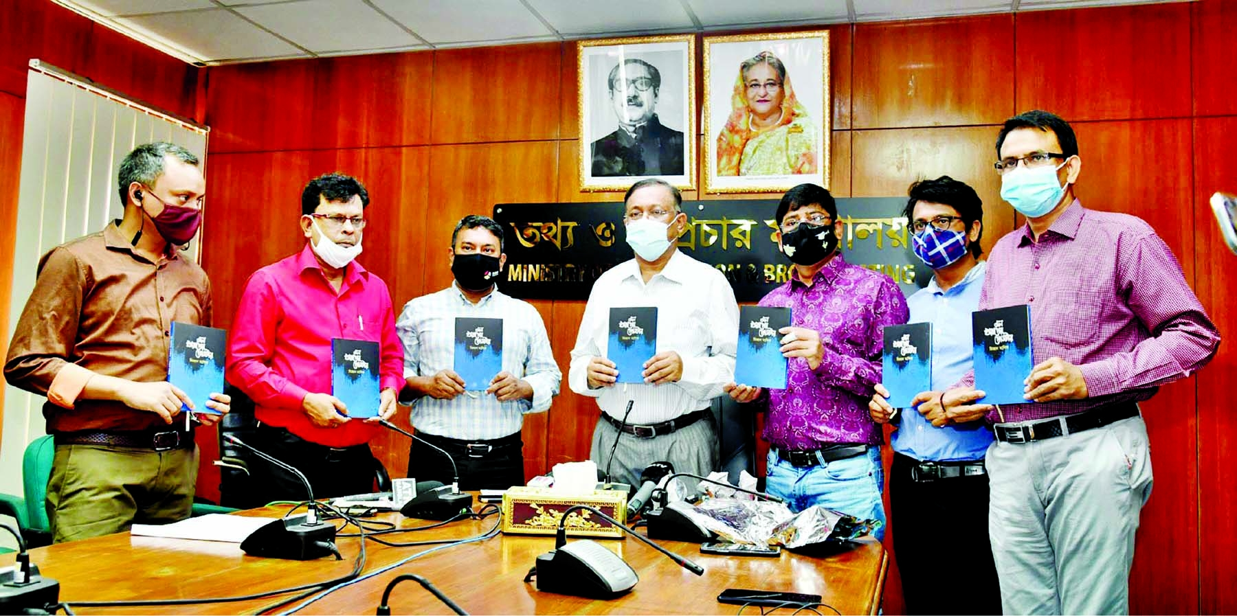 Information and Broadcasting Minister Dr. Hasan Mahmud, among others, holds the copies of a book titled 'Mon Kharaper Poster' at its cover unwrapping ceremony in the seminar room of the ministry on Monday.