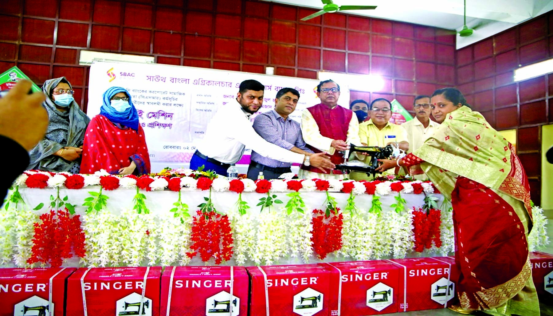 SBAC Bank Chairman SM Amzad Hossain along with ANM Faizul Haque, Deputy Commissioner of Bagerhat distributing sewing machines among 100 women under the bank's CSR fund at Fakirhat Upazila Prishad in Bagerhat on Sunday. Senior officials of the bank and local elites were present.