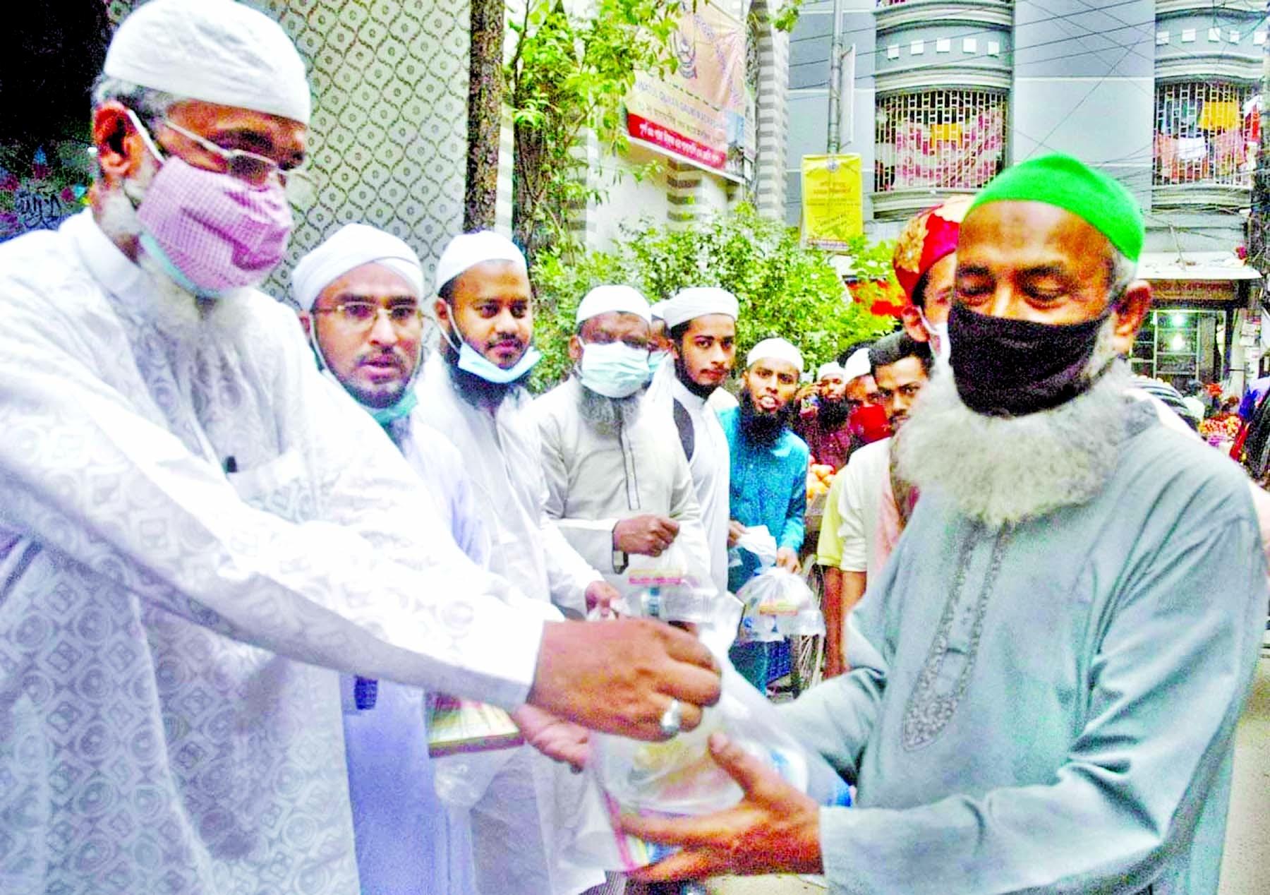 President and Senior Vice-President of Islami Sramik Andolon, Dhaka City South Alhaj Zahangir Alam and Siddiqur Rahman respectively distribute iftar among the destitute at Agamosi Lane area in the city on Tuesday.