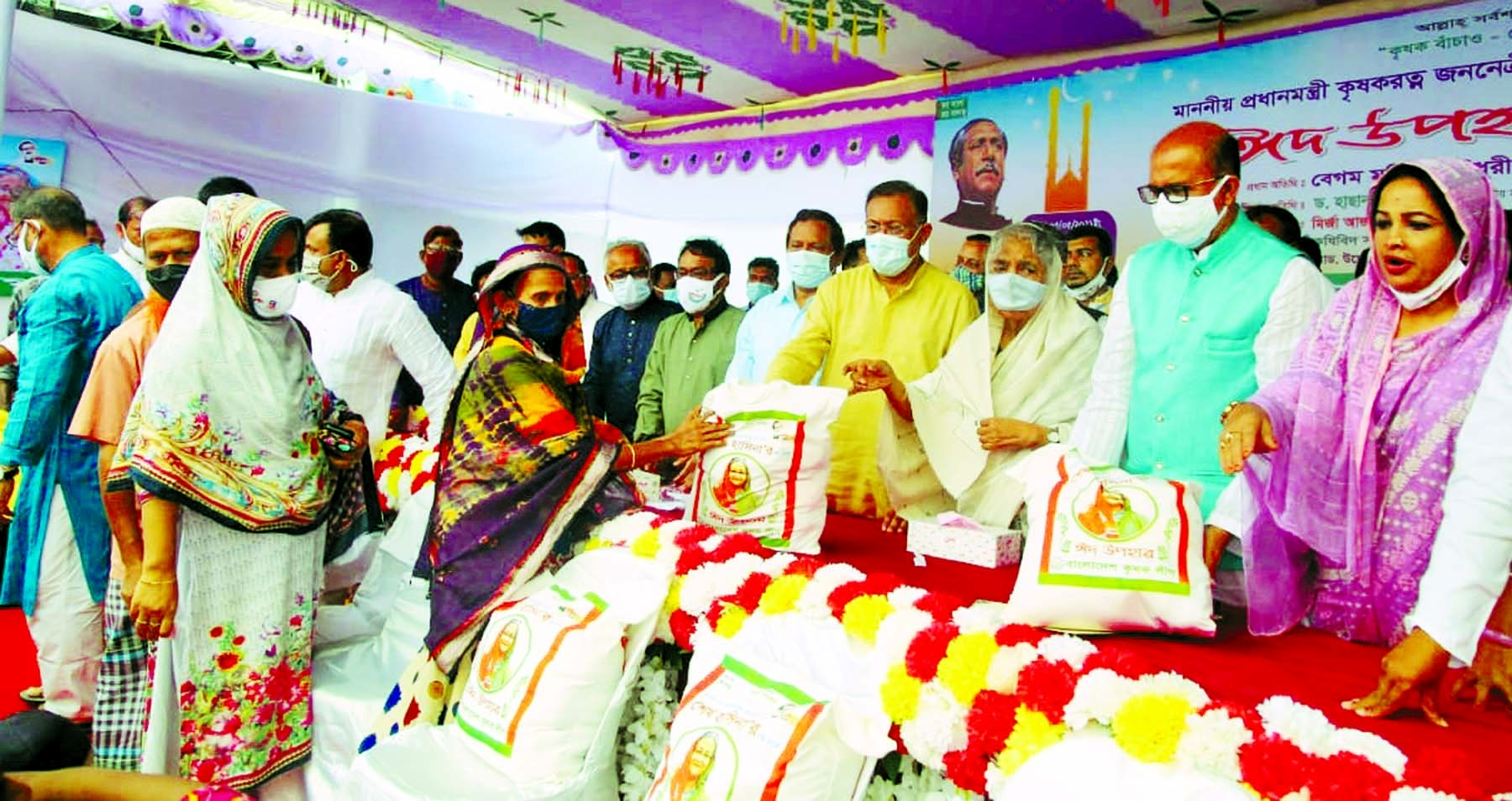 Information and Broadcasting Minister Dr. Hasan Mahmud distributes Prime Minister's Eid gifts among the poor people at a function organised by Bangladesh Krishak League at Bangabandhu Avenue in the city on Wednesday.