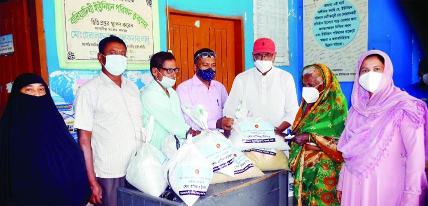 Mahbubur Rahman Mahbub, Chairman of Baliadighi Union Parishad of Bogura Gabtoli distributes PM's grants and masks among 250 poor, distressed families of the locality on Tuesday.
