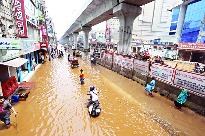 People wade through a waterlogged street at Begum Rokeya Sarani, Mirpur, in the capital Dhaka. Heavy monsoon rain lashed the capital on Saturday morning, inundating low-lying areas and disrupting road traffic.