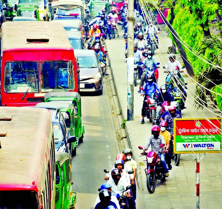 Bikers move to and fro footpath to sidetrack traffic jam violating traffic rules at Satrasta of Tejgaon in the capital on Thursday.