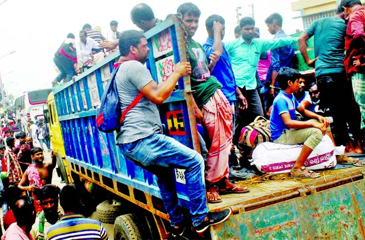 People take rides on trucks in the capital's Gabtoli area on Sunday, ignoring the life risk on their way to village homes ahead of Eid-ul-Azha.