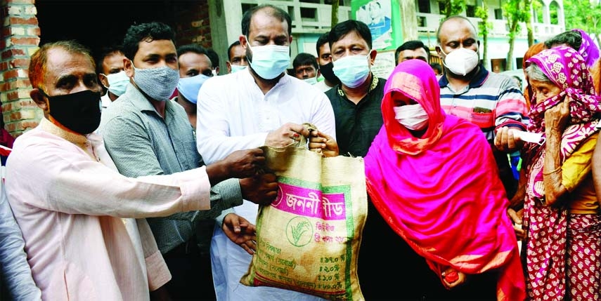 Chairman of Bogura Kagoil Union under Gabtoli upazila, Aga Nehal Bin Jalil Tapon distributes 10 kg of rice each among one thousand 230 people of the union allotted by the Relief Ministry on the occasion of Eid and Corona pandemic at a distribution program held at a local high school ground on Sunday.