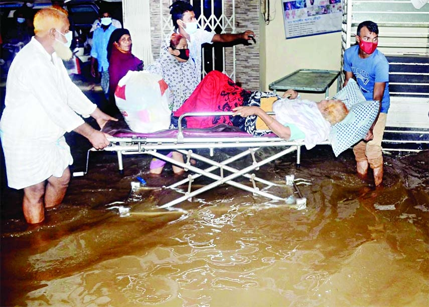 Two people take a Covid patient lying on a stretcher in a waterlogged space  in front of Ma O Shishu Hospital at Agrabad area in Chattogram on Saturday after a short spell of rain.