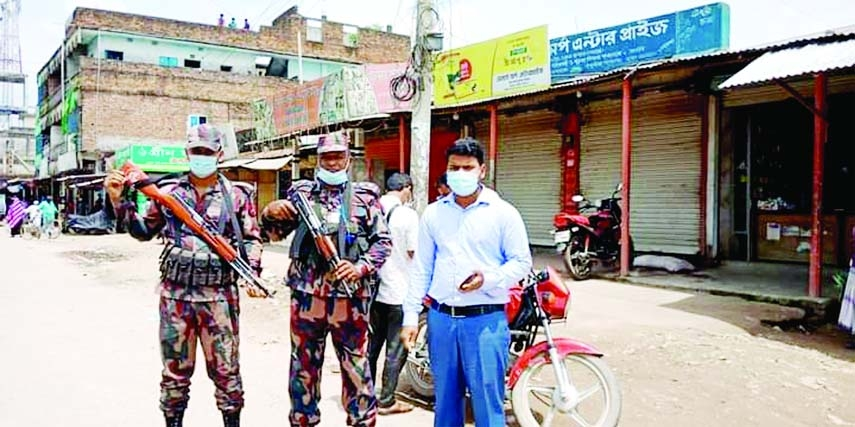 Collectorate Executive Magistrate of Kishoreganj Obidur Rahman Sahel is seen patrolling with BGB members to implement the nation-wide lockdown in various hat bazaars in Pakundia Upazila on Monday.