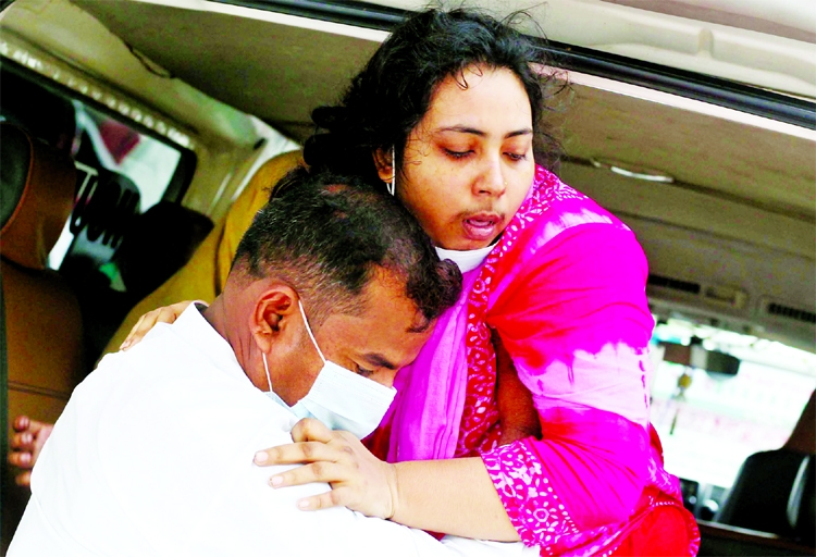 A man carries a coronavirus patient to the Dhaka Medical College Hospital. They came from an outlying district on Friday.