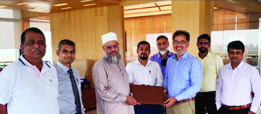 Hasan Mahmud Raja of United Group Limited and Zillul Karim of Credence Housing Limited, exchanging document after signing an agreement to develop two multi-storied buildings at Mohammadpur in the capital. Top officials from both sides were present.