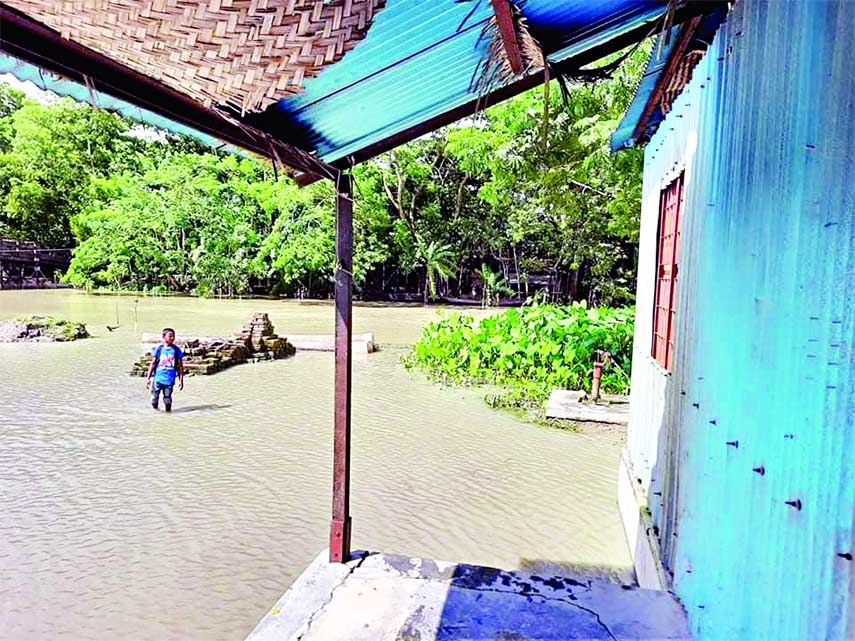 A boy wades through flood water to attend classes at Abul Hossain Government Primary School at Mehendiganj upazila in Barishal district on Tuesday.