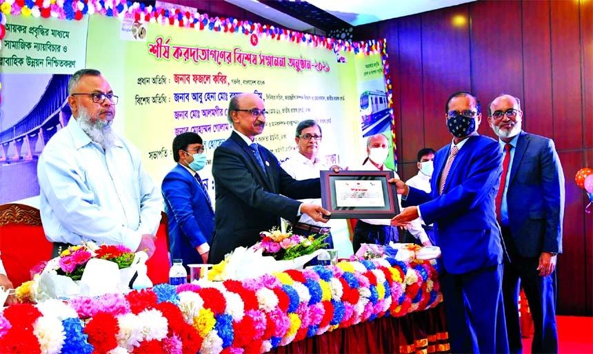 Abul Kashem Md Shirin, Managing Director & CEO of Dutch-Bangla Bank Ltd, receiving Certificate of Honor from Fazle Kabir, Governor of Bangladesh Bank, at a city hotel on Tuesday.