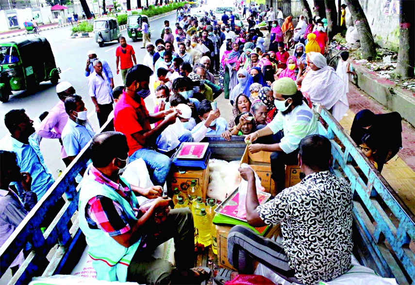 People stand in long queues to purchase TCB's open market sale products at a cheaper rates. This photo was taken from Abdul Goni Road in the capital on Monday.