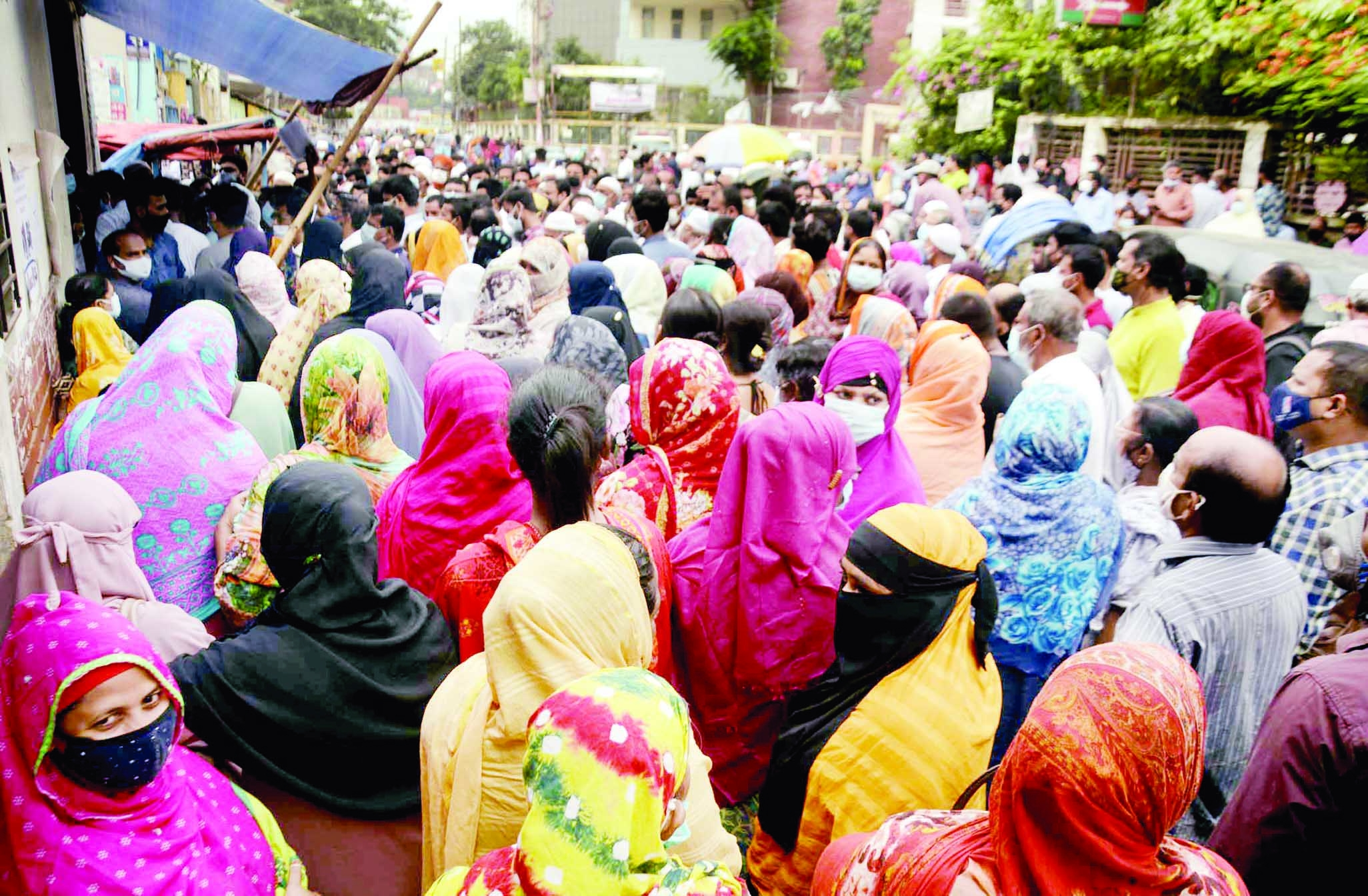 Hundreds of people crowd in front of a Covid-19 vaccine centre at Mugda in the capital on Tuesday.
