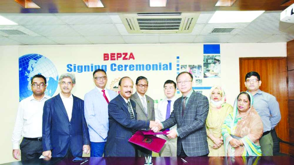 Ali Reza Mazid, Member (Investment Promotion) of Export Processing Zones Authority (BEPZA) and Chen Shu Qiang, Senior Operation Manager of Meigo (BD) Limited, exchanging document after signing an agreement on behalf of their respective organizations at BEPZA Complex in the capital on Wednesday. Under the deal, the Chinese company will establish a toy manufacturing industry in Dhaka EPZ with an investment of $6.55 million. Top officials from both sides were present.
