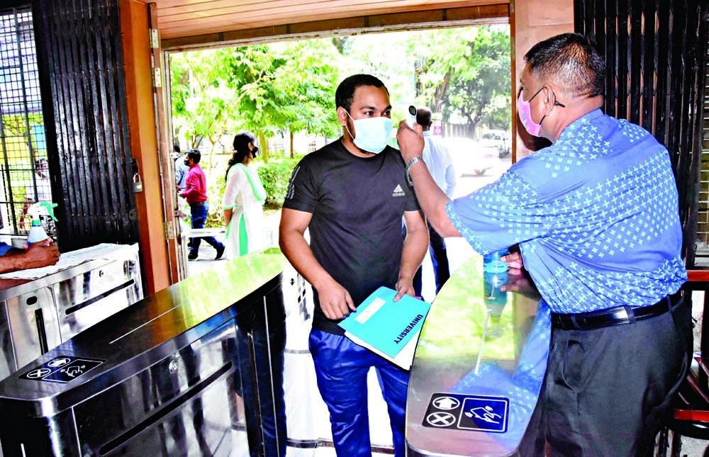 A student has his body temperature checked before entering the central library of Dhaka University on Monday amid falling Covid-19 infections in the country.