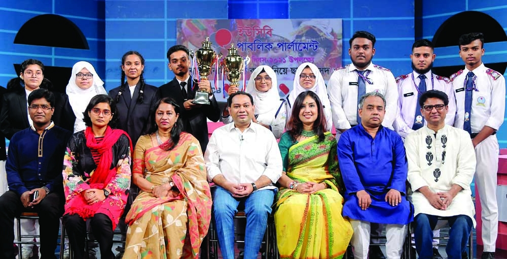 Guest of Shadow Parliament with the reason of child marriage growth Farida Yasmin and Debate for Democracy Hassan Ahamed Chowdhury Kiron are seen with the debating participants of champion and runner up teams with trophies in hand at FDC in Tejgaon on Friday.