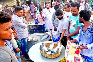 Wholesalers throng the large fish market of Mawa in Louhagonj upazila of Mushiganj district on Monday from different parts of the country for purchasing fish .