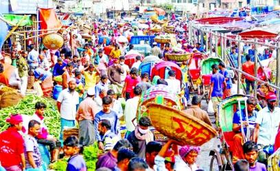 Porters and day-labourers all out to earn their livelihood as transactions are on at a kitchen market in Dhaka on Monday.