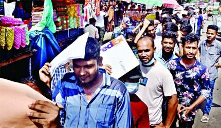 Expatriates stand in long queues in order to receive 2nd Covid vaccine doses in front of the Dhaka Medical College Hospital on Sunday.